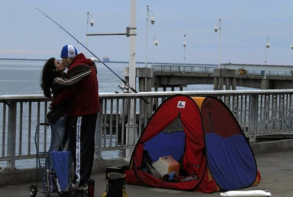 Ana Aguilar and Rene Angeles share a tender moment while fishing at the Belmont Veterans Memorial Pier.