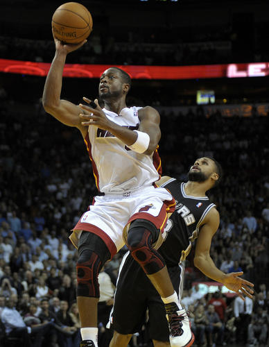Miami Heat guard Dwyane Wade scores in front of San Antonio Spurs guard Patty Mills during the fourth quarter of their game.