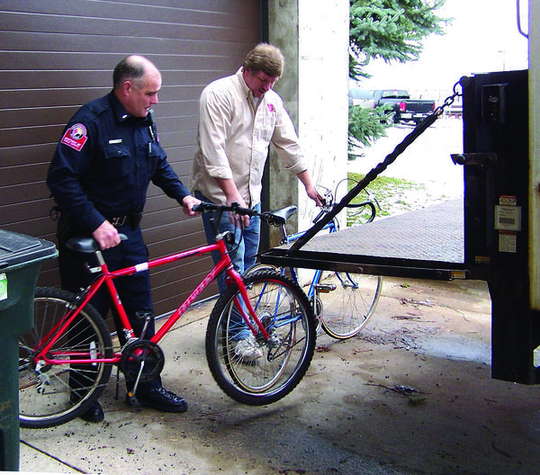 Lt. Matthew Breed of the Petoskey Department of Public Safety (left) and Salvation Army assistant manager Brian Miller load a couple of the 21 bicycles donated by the department onto a Salvation Army truck on Thursday morning at Petoskey City Hall.