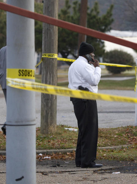 Hampton Police Detective W. Owens on Friday stands behind crime scene tape at the scene of Thursday night's homicide at Roy's Quickserve.Mohammad Zidan, 50, a clerk at Roy's Quickserve, was killed on the night of Nov. 29 after being shot multiple times during a robbery at the Hampton convenience store on the 2100 block of West Pembroke Avenue.