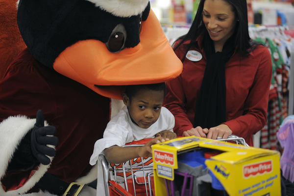On a shopping spree hosted by Baltimore Orioles center fielder Adam Jones, Jeremiah Harris, 5 reacts as the Orioles Bird puts his beak over his head during shopping for two families at a Target shopping center Thursday, Nov 29, 2012. Jones, who recently garnered a second Gold Glove award, treated the families through OriolesREACH, to a round of shopping for toys and clothing.