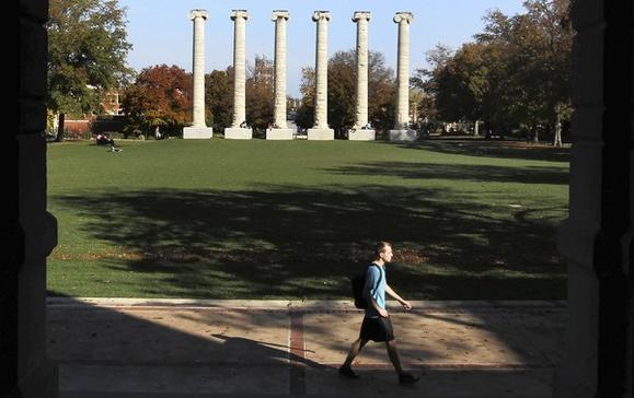 A student strolls the University of Missouri campus. In the background are the six columns that once supported Academic Hall.