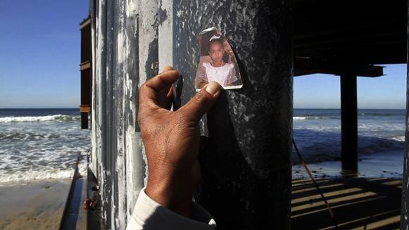 On the Tijuana side of the border fence, Luis Ernesto Rodriguez, 43, holds up a tattered snapshot of one of his young daughters. He was here when one of his attorneys delivered news about his long fight to be reunited with them.