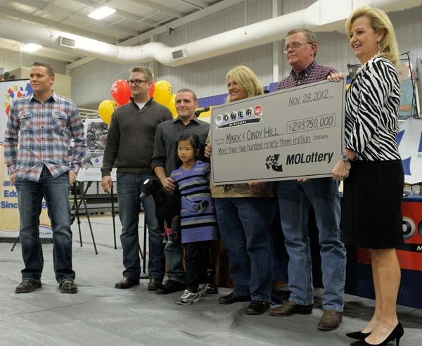 The Hill family holds an oversized check presented by Missouri Lottery director May Scheve (R) during a news conference at the North Platte High School in Dearborn, Missouri, November 30, 2012. The Hill family bought one of the two winning tickets for a record $588-million Powerball lottery from the Trex Mart truck stop in Dearborn, Missouri. (L-R) Sons Jason, Cody, Jarod, adopted daughter Jaiden, and Cindy and Mark Hill.