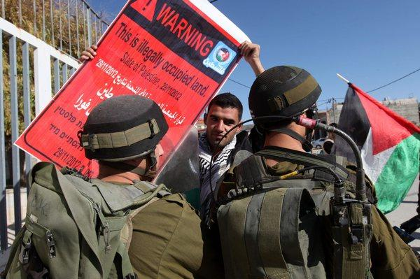 A Palestinian youth holds a placard as he faces Israeli soldiers during a demonstration Friday in the West Bank village of al-Masara against Jewish settlements in the West Bank.