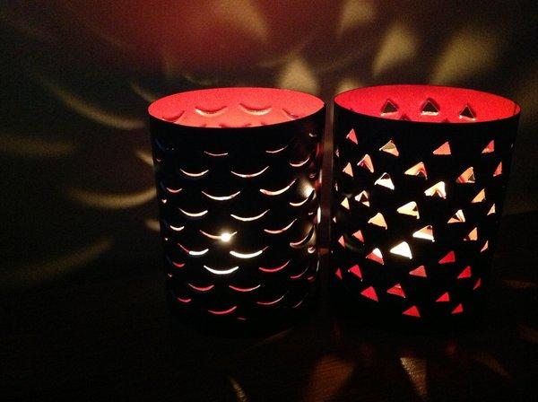 Punched metal candle holders from Made by DWC glow in varied patterns. The pieces are matte black on the outside, glossy colors on the inside. In daylight, the ones here are orange.