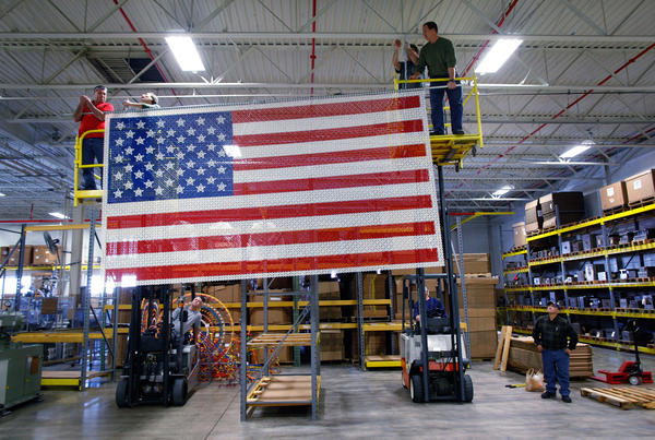 Employees of The Rodon Group, a plastic injection molder that makes K'NEX building toys in Hatfield Pa., raises a flag consisting of 49,000 K'NEX pieces in preparation for a visit by President Obama.