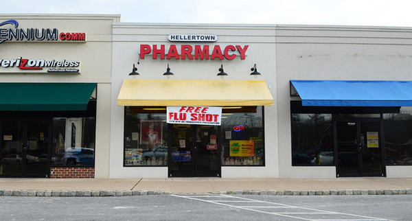 Federal authorities raided a Hellertown drug store and charged two of its pharmacists with being part of a $13 million scheme in which prescription painkillers were sold over the Internet.