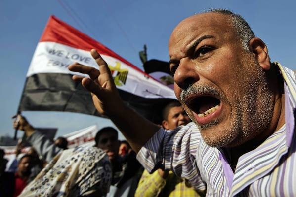 A protester shouts in Cairo's Tahrir Square, where demonstrators denounced the expanded powers of President Mohamed Morsi and the passage of a draft constitution they say doesn't represent all Egyptians.