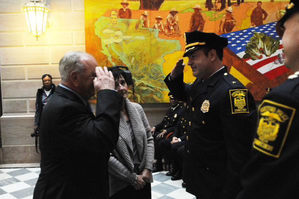 New Hartford Police deputy chief William F. Long III, right,  salutes at his father, former Naugatuck Police Chief William Long, Jr., as mother Susan Long looks on Friday afternoon at Hartford City Hall.