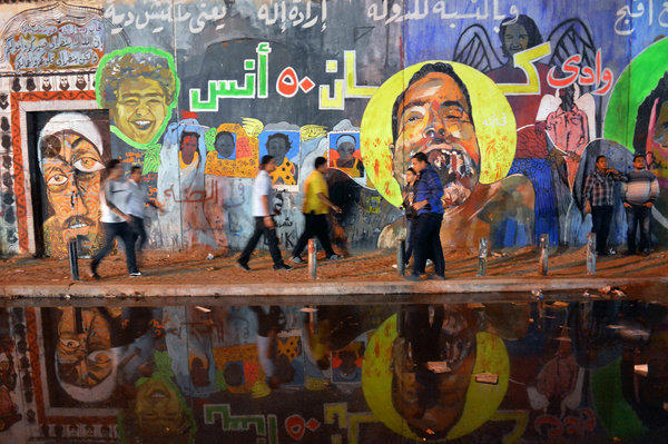 Egyptians pass by graffiti on the walls of Mohamed Mahmud Street in Cairo's landmark Tahrir Square on Nov. 30, 2012.