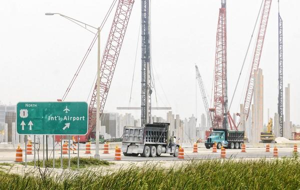 Traffic on U.S. 1 passes dozens of concrete pillars that are part of the bridge construction that will allow the new south runway to slope upward and across U.S. 1. Twenty-six hundred pillars, varying in height from 50 to 100 feet, will eventually be buried in the runway's foundation.