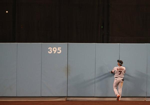 Juan Rivera hits a home run in the Dodgers' 2012 season finale as Giants center fielder Gregor Blanco looks on at Dodger Stadium.