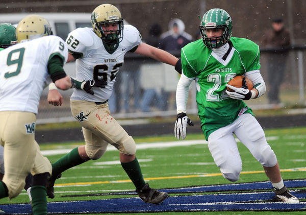 As snow flurries fall, Wyoming Area High School's Joe Erzar (62) reaches for Pen Argyl Area High School's Mike DePaolo (22) running downfield during the PIAA Class 2A first-round football game on Saturday at Northern Lehigh's Bulldog Community Stadium in Slatington.