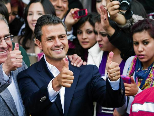 Enrique Peña Nieto shows his ink-stained thumbs after voting in the presidential election in July. His victory returns the long-ruling PRI to power.