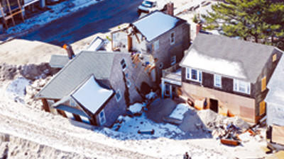 People stand near damaged homes on Nov. 9 along the Atlantic Ocean in New Jersey after the region was pounded by Superstorm Sandy.