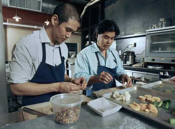 Todd Chang, cooks apprentice, and Chef Gary Menes at Le Comptoir in Glendale prepare for dinner. The restaurant is in the historic Bekins Storage building.
