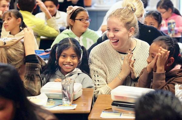 Sage Hill High's Kylie Gaughan, 18, second from right, shares a laugh with fourth-graders Celia Acuna, far right, and Lisset Ramirez, left, during a visit to Pomona Elementary's after-school program, Project Success, on Friday.