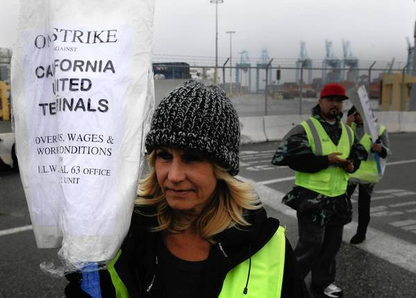 A clerical workers union member walks a picket line at the Port of Los Angeles. Other unions are honoring the picket lines at the ports of Los Angeles and Long Beach, virtually shutting them down.