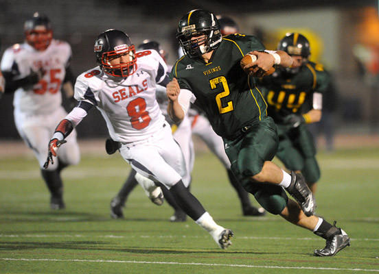 Central Catholic's Colin McDermott (right) looks for room to run past Selinsgrove's Tyler Krebs (left) during the quarterfinal round of the PIAA 3A football playoffs in Bethlehem Friday night.