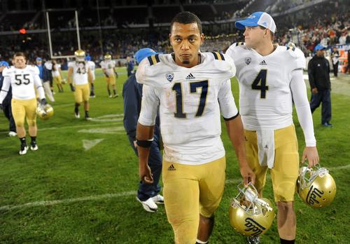 Bruins quarterback Brett Hundley walks off the Stanford Stadium field ahead of reserve quarterback Kevin Prince after a 27-24 loss to the Cardinal on Friday night.