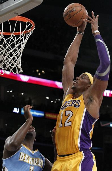 Lakers center Dwight Howard dunks over Nuggets forward Jordan Hamilton in the first quarter on Friday.