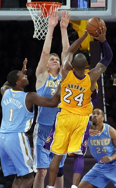 Lakers guard Kobe Bryant goes strong to the basket against Nuggets defenders Jordan Hamilton, left, Timofey Mozgov and Andre Miller in the fourth quarter on Friday.