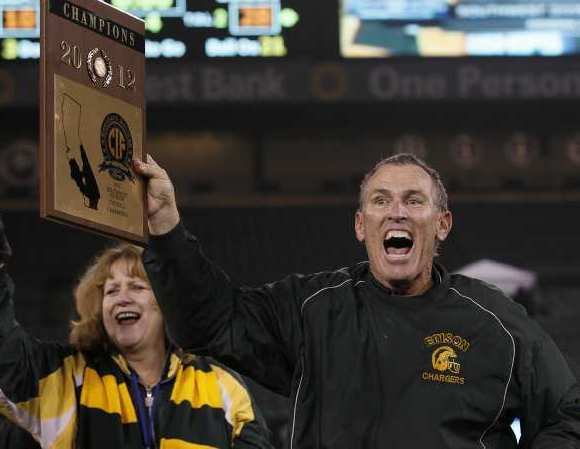 Edison head coach Dave White flanked by the Principal D'Liese Melendrez shows off the CIF Southern Section Southwest Division championship plaque after beating Villa Park at Angel Stadium on Friday.