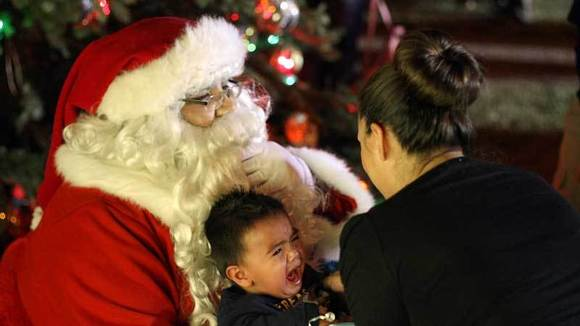 Crystal Davila (right) comforts her son, Aaron Davila, 1, who's crying sitting on the lap of Santa Claus