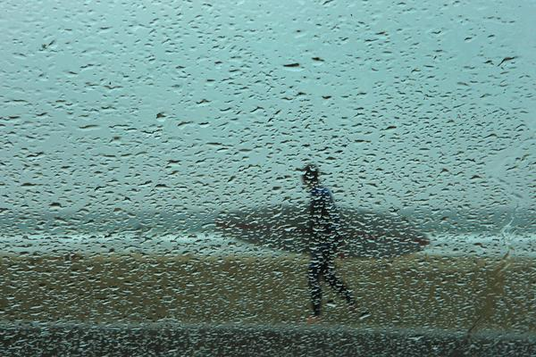 A surfer is viewed through a pattern of raindrops on a windshield in Newport Beach.