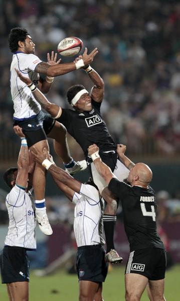 New Zealand's players jump to catch the ball from a line out against Samoa's players during their Sevens World Series Cup final rugby match at The Sevens stadium in Dubai December 1, 2012.