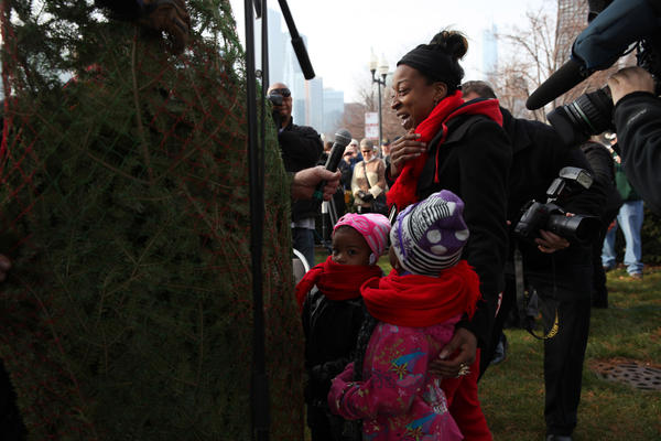 Tiffany Buford and her two daughters Ryanna Buford, 4, left, and Desirae Rucker, 6, receive a free Christmas tree from the annual U.S. Coast Guard Mackinaw Cutter's visit at Navy Pier on Saturday.