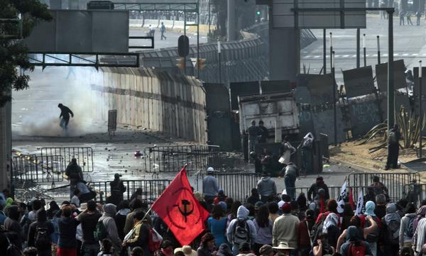 Rioters clash with police officers before the inauguration ceremony of incoming Mexican President Enrique Pena Nieto on December 1, 2012, in Mexico City. Pena Nieto was sworn in as president of Mexico on Saturday following protests by leftist lawmakers inside the congress and clashes between demonstrators and police outside.