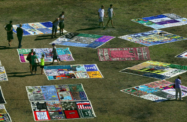 People walk by and take a look at panels from the AIDS Memorial Quilt on display on the lawn of the Riverside Hotel in Fort Lauderdale.  The quilt is on display in observance of World AIDS Day. The handmade tapestry weighs 54 tons and is composed of more than 48,000 panels and holds 24,318 signatures and dedications to more than 94,000 people.