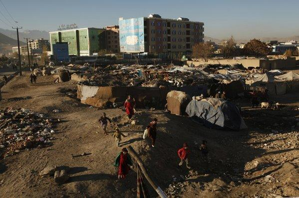Young Afghans run near one of the makeshift camps for the displaced around Kabul, where more than 30,000 people have settled in illegal camps in search of jobs and shelter, according to the Office of the United Nations High Commissioner for Refugees