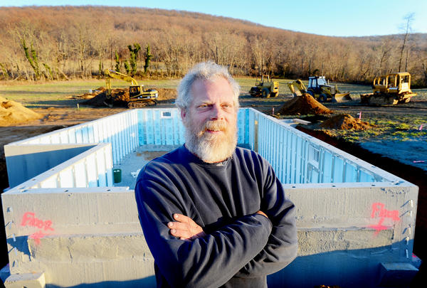 Michael Betson stands near the foundation of his new home which is under construction in Brownsville, Md.