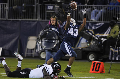 Uconn running back Lyle McCombs reaches for a pass along the sideline over Cincinnati linebacker Maalik Bomar. The pass was ruled incomplete because McCombs stepped out of bounds.