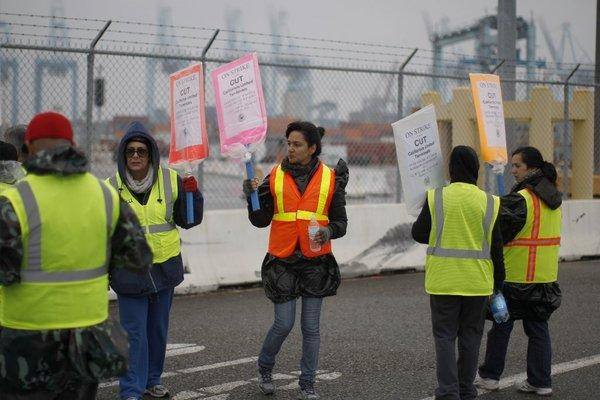 Striking workers carry pickets outside the APM Terminal at the Port of Los Angeles. Talks aimed at resolving the 5-day-old strike were continuing on Saturday.