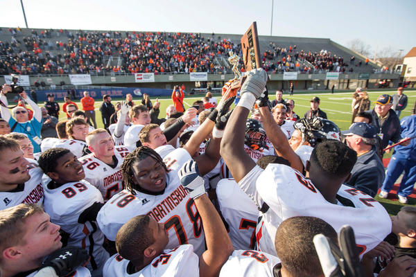Martinsburg players hoist the West Virginia Class AAA championship trophy in Wheeling, W.Va., on Saturday after defeating Cabell Midland 38-14 in the state final.
