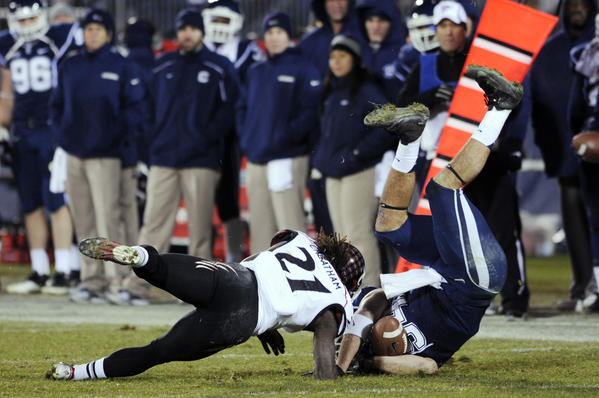 Connecticut Huskies tight end Ryan Griffin is brought down hard after a catch against Cincinnati Bearcats defensive back Camerron Cheatham (21). Griffin left the game with assistance after the play, but came back to play again.