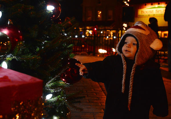 Ryder Hoffman, 17 months, of Emmaus points to the glowing Christmas tree in Emmaus' triangle during Emmaus' Old Fashioned Christmas on Saturday night. the event featured a tree lighting, carol singing, and a visit from Santa.
