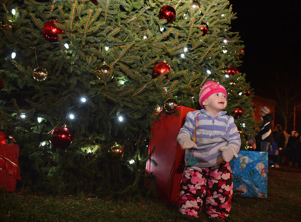 Autumn Diehl, of Macungie stands near the Christmas tree in Emmaus' triangle during Emmaus' Old Fashioned Christmas on Saturday night. the event featured a tree lighting, carol singing, and a visit from Santa.