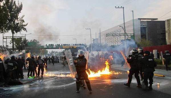 Police and protesters clash outside the Congress building in Mexico City before Enrique Peña Nieto is inaugurated as president.