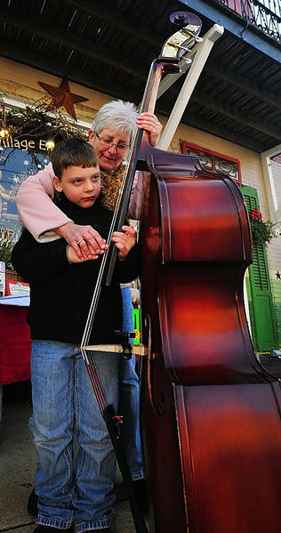Max Young got the attention of upright bass player Jean Koons Saturday during Smithsburg Hometown Christmas. Koons let Max pluck the strings to a holiday song. Koons plays with Little Sister Band.