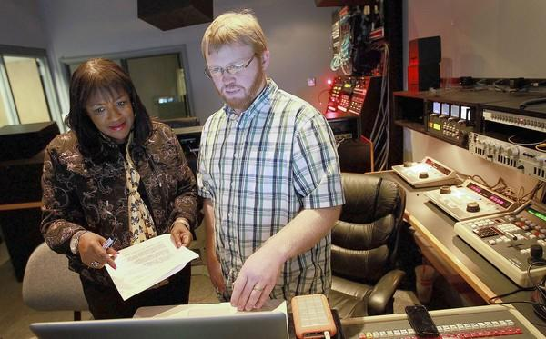 Ann Stephens-Cherry, Hampton City Schools director of marketing and public relations, talks with video producer Andy Foley about a project in their production studio Tuesday.