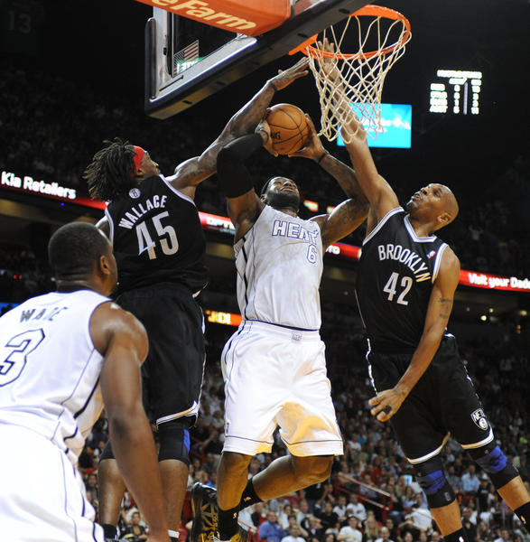 LeBron james gets fouled as Jerry Stackhouse (42) and Gerald Wallace defend for the Nets on the play.