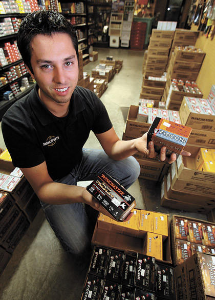 A.J. Hoffman, owner of Sodak Sports, holds two boxes of shotgun shells that differ in weight. The Fiocchi box is a lighter weight load, which hunters would have used earlier in the pheasant hunting season. The Winchester box is a heavier load, which hunters will use now as the birds' feathers have thickened with colder weather and the birds take flight sooner, making the hunter's shot longer.