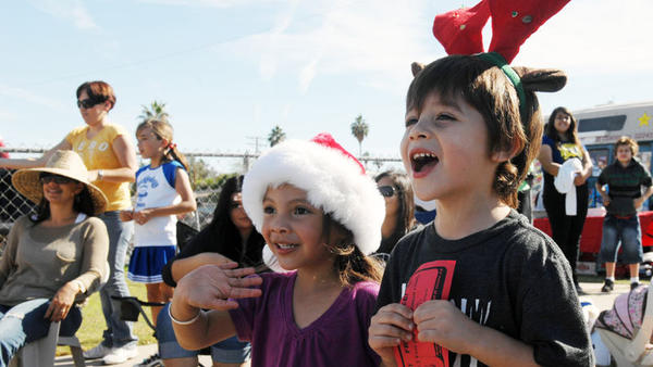 FROM LEFT: Peyton Garcia, 3, and Zayden Petree, 4, cheer for Santa Claus at the 67th annual  Los Vigilantes and El Centro Chamber of Commerce Christmas Parade on Saturday morning  in El Centro.