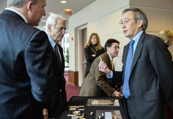 Jeff Chamberlain, left, deputy director, and George Crabtree, director of the Joint Center for Energy Storage Research, demonstrate prototype batteries to U.S. Energy Secretary Steven Chu, right. Chu on Friday announced that the Department of Energy would accelerate battery development through Argonne National Laboratory in Lemont.