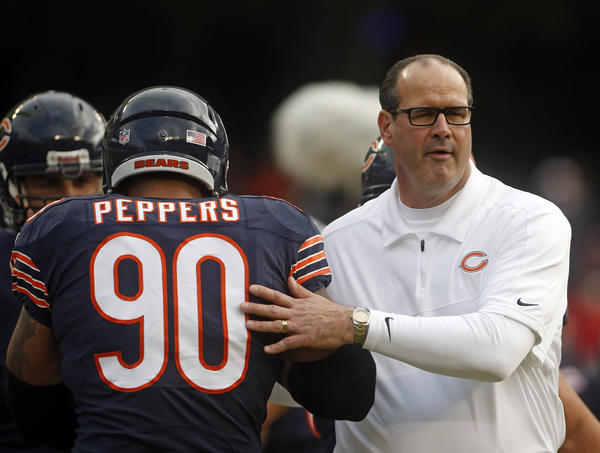 Chicago Bears defensive end Julius Peppers (90) and offensive coordinator Mike Tice prepare for the game Sunday at Soldier Field.